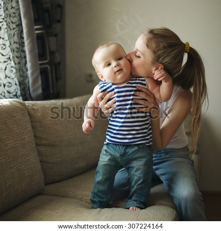 beautiful young mother with baby at home - stock photo