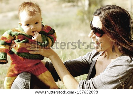 beautiful young mother with cute baby outdoor - stock photo
