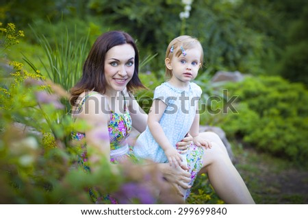 Beautiful young mother with daughter having fun in summer park - stock photo