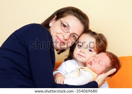 Beautiful young mother with her adoroble children - stock photo