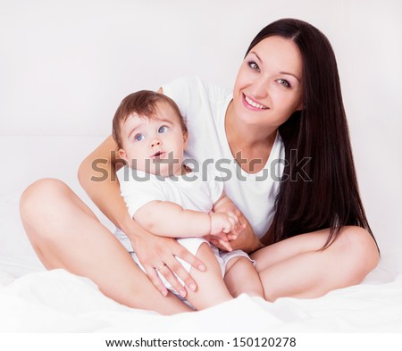 beautiful young mother with her baby in bed at home - stock photo