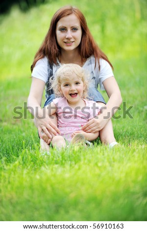 Beautiful young mother with her  daughter l sitting on grass . summer.