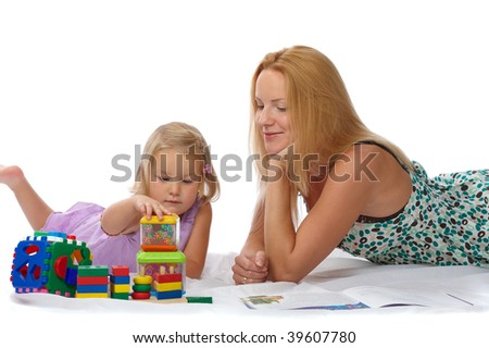 beautiful young mother with her daughter lying on the floor and play with toys
