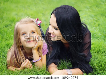 Beautiful young mother with her five years old daughter laying on the grass - stock photo