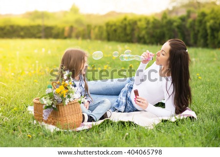 Beautiful young mother with her five years old daughter laying on the grass,and playing with bubbles,colored photo - stock photo