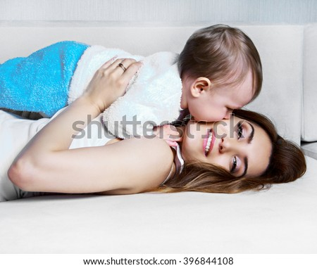 beautiful young mother with her one year old son at home - stock photo