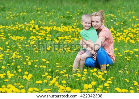 Beautiful young mother with her son playing on grass . summer day