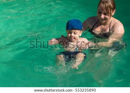 beautiful young mother with son in water