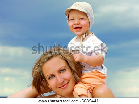 beautiful young mother with son on the beach
