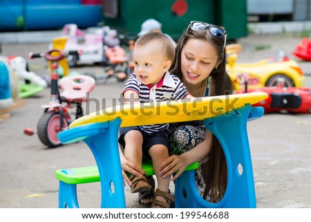 beautiful young mother with son play on playground - stock photo
