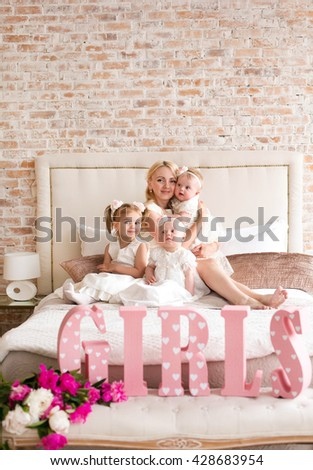 beautiful young mother with three daughters Happy family of mother with three daughters Ã??Ã?? stylish interior. Fashion style studio portrait. - stock photo