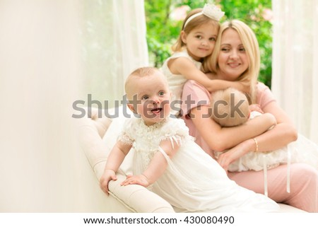 Beautiful young mother with three daughters Happy family of mother with three daughters in the yard in stylish interior. Fashion style street portrait. - stock photo