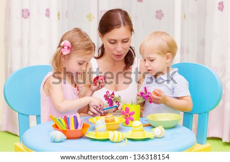 Beautiful young mother with two sweet kids decorated traditional Easter eggs with colorful paint, happy family concept
