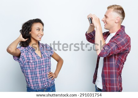 Beautiful young mulatto girl standing posing while her smiling blond boyfriend making her photos on his smartphone, isolated on grey background