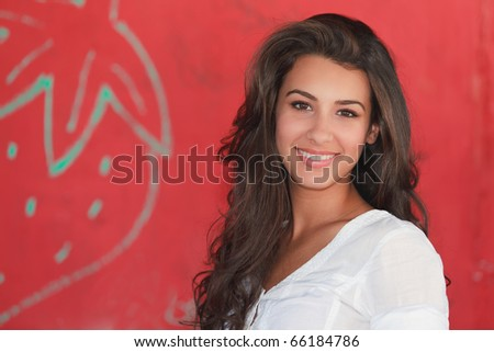 Beautiful young multicultural woman in an outdoor lifestyle pose with a red background. - stock photo