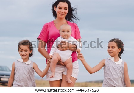 Beautiful young mum and her Children walking in Park together. Happy family. - stock photo