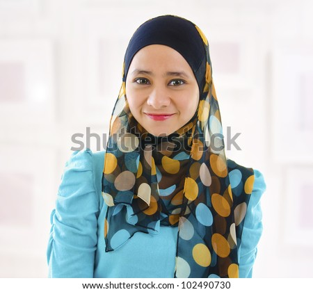 Beautiful Young Muslim girl smiling, indoor. - stock photo