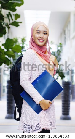 Beautiful young muslim student holding a file and backpack