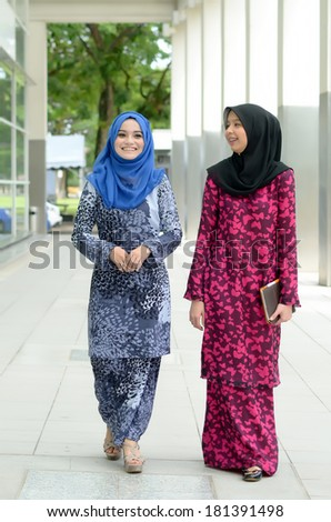 beautiful young muslim walking together to university - stock photo