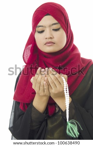 Beautiful young Muslim woman being pray over on white background. - stock photo
