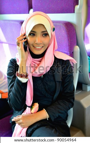 beautiful young muslim woman in a train smiling and making a phone call