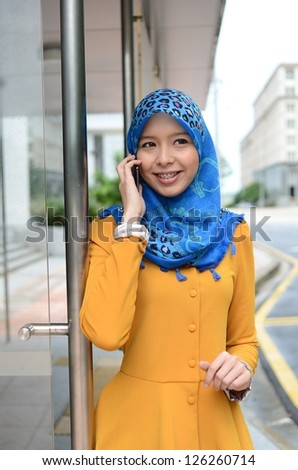 Beautiful young muslim woman messaging on mobile phone
