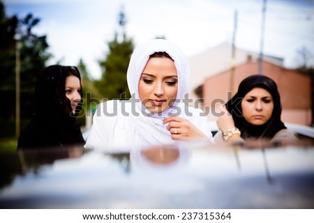 Beautiful young muslim woman. Muslim bride before wedding, wearing white hijab in front of mosque. Sharia wedding. - stock photo