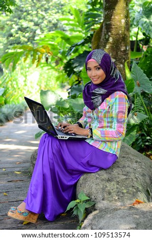Beautiful young muslim woman smile with laptop