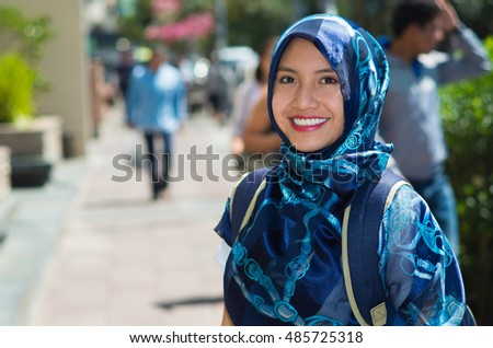 Beautiful young muslim woman wearing blue colored hijab and backpack, posing happily in street smiling to camera, outdoors urban background