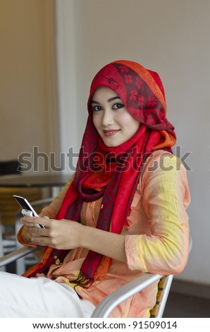 beautiful young muslim woman with stylish scarf sending text messaging  in the coffee shop - stock photo