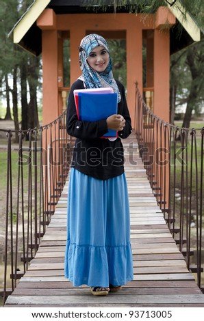 beautiful young muslimah woman with head scarf holding the books and standing on hanging bridge at recreation park - stock photo