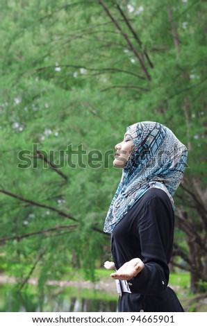 beautiful young muslimah woman with stylish appreciate the beauty of nature while breathing the fresh air - stock photo