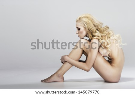 Beautiful young naked woman sitting - stock photo