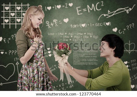 Beautiful young nerd girl gets flowers from her boyfriend in a classroom - stock photo