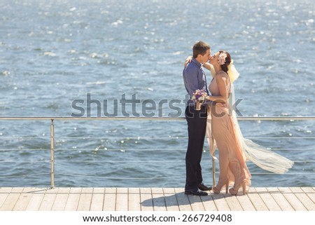 beautiful young newlywed couple on wooden bridge near sea embracing and kissing - stock photo