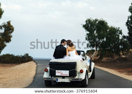 Beautiful young newlyweds on the wedding walk with the car - stock photo