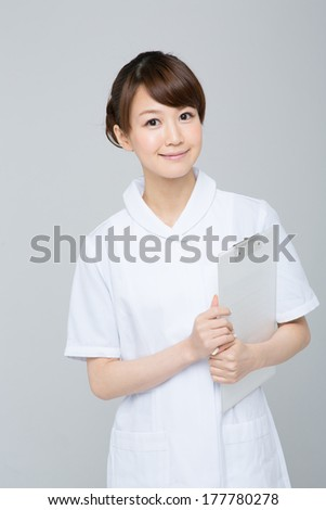 Beautiful young nurse on gray background  - stock photo