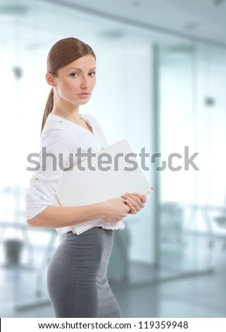 Beautiful young office lady holding a white folder in her hands