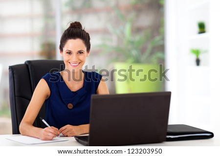 beautiful young office worker sitting by office desk - stock photo