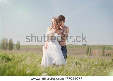 beautiful young pair kissing and hugging on green grass - stock photo