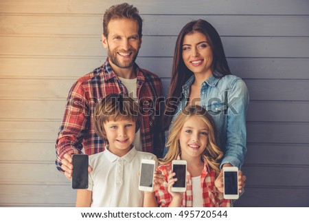 Beautiful young parents and their children are holding smartphones, looking at camera and smiling, on gray wall background