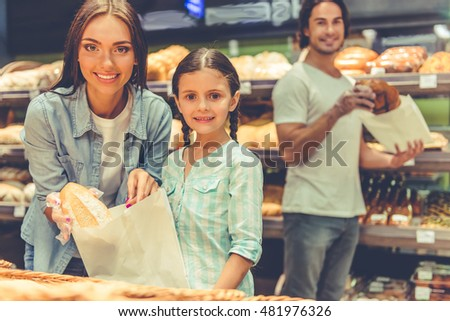 Beautiful young parents and their cute little daughter are looking at camera and smiling while choosing baking in the supermarket