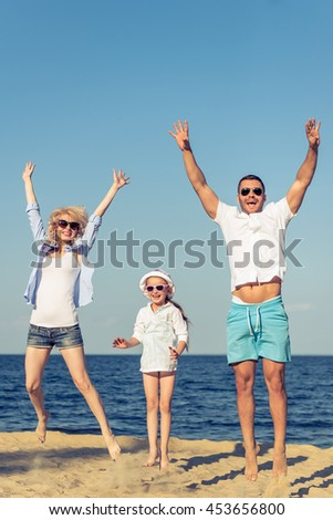 Beautiful young parents and their cute little daughter in casual clothes and sun glasses are looking at camera and smiling while jumping on the sunny beach - stock photo