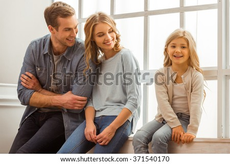 Beautiful young parents looking at their pretty little daughter and smiling while sitting near the window at home - stock photo