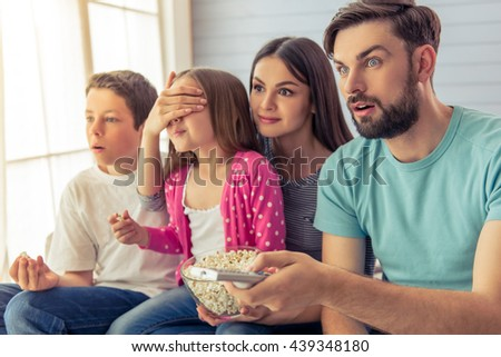 Beautiful young parents, their  daughter and son are watching TV, eating popcorn and showing surprise. Mom is covering er daughter's eyes