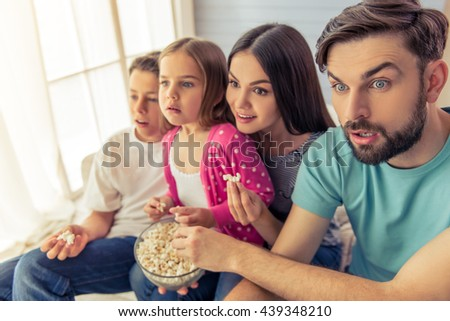 Beautiful young parents, their  daughter and son are watching TV, eating popcorn and showing surprise, sitting on sofa at home - stock photo