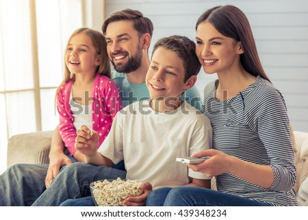 Beautiful young parents, their  daughter and son are watching TV, eating popcorn and smiling, sitting on sofa at home. Mom is using a remote control - stock photo