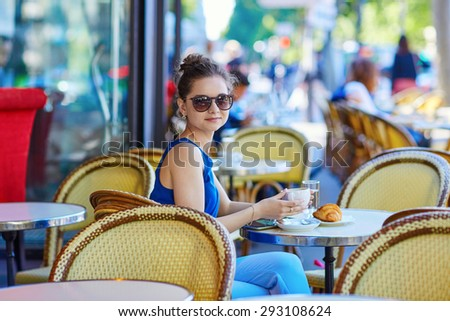 Beautiful young Parisian woman in blue blouse drinking coffee in an outdoor cafe on a summer day - stock photo