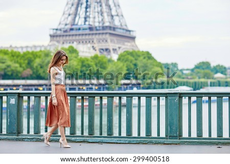 Beautiful young Parisian woman in long brown silk skirt near the Eiffel tower on a summer day - stock photo