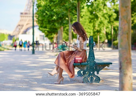 Beautiful young Parisian woman in long skirt near the Eiffel tower on a summer day, sitting on the bench and using mobile phone
